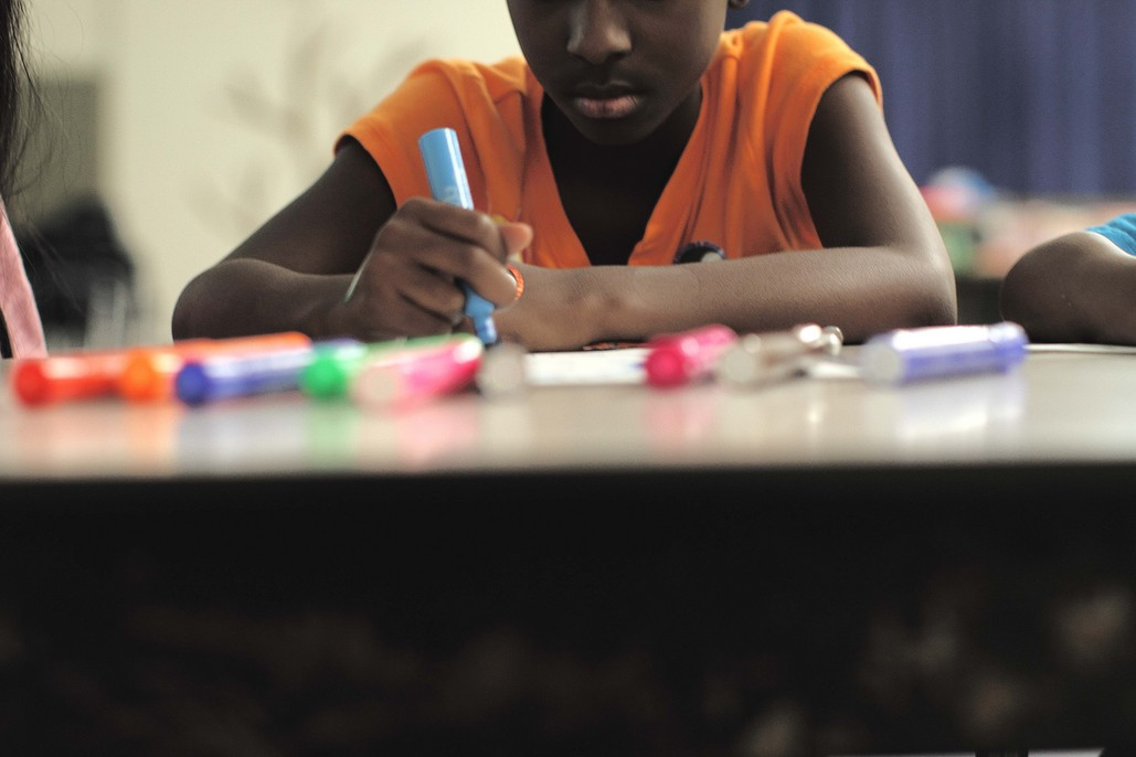 Child coloring with a marker