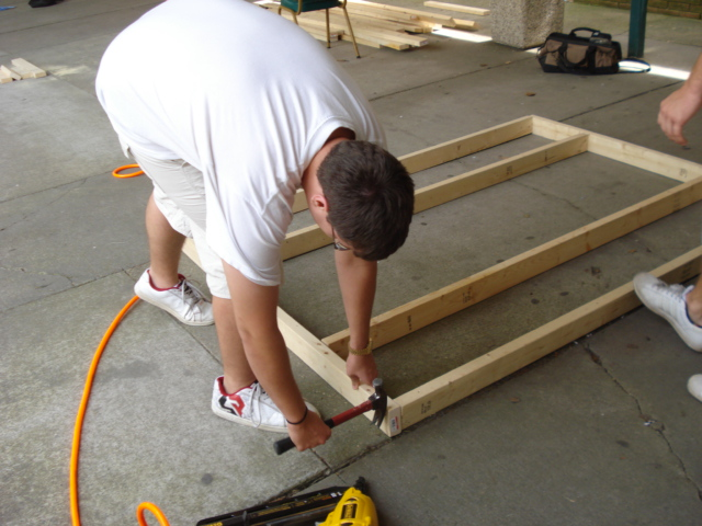 Young person building a wood frame