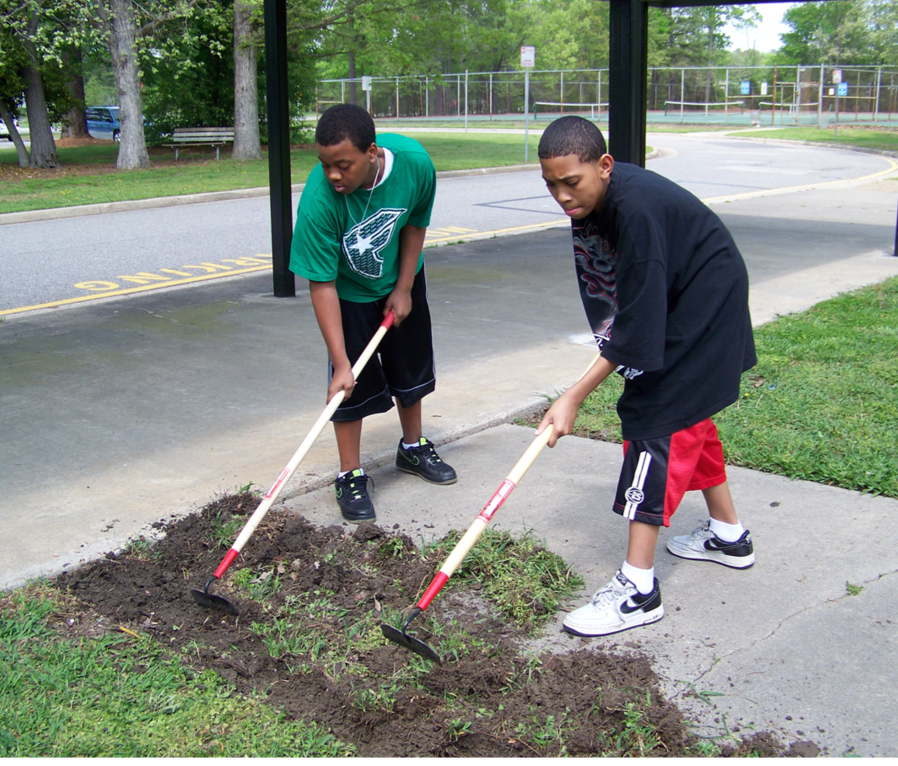 Students rake grass and weeds