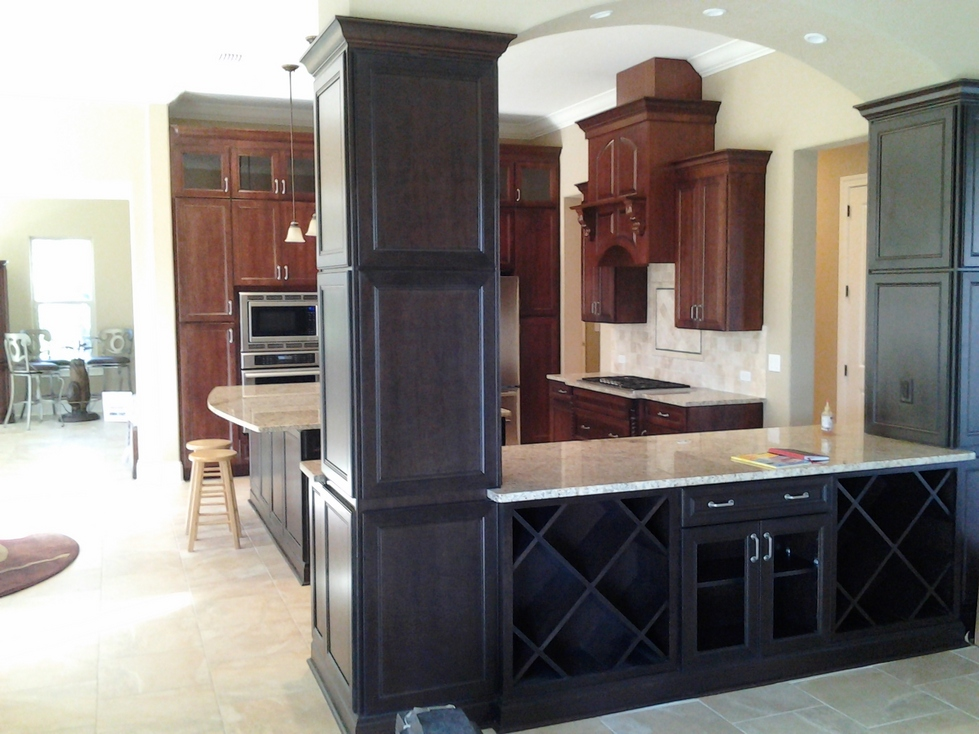 Custom bar and wine cabinets with dark brown stained crown moulding and trim