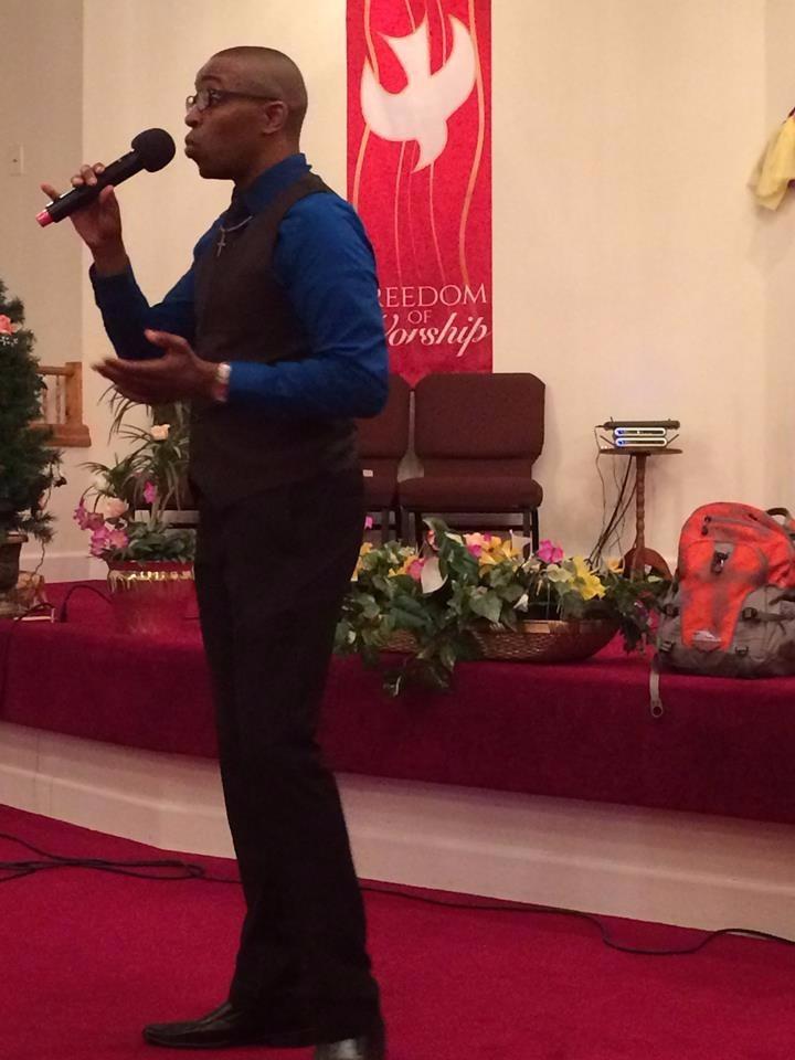 Janard in blue shirt preaching