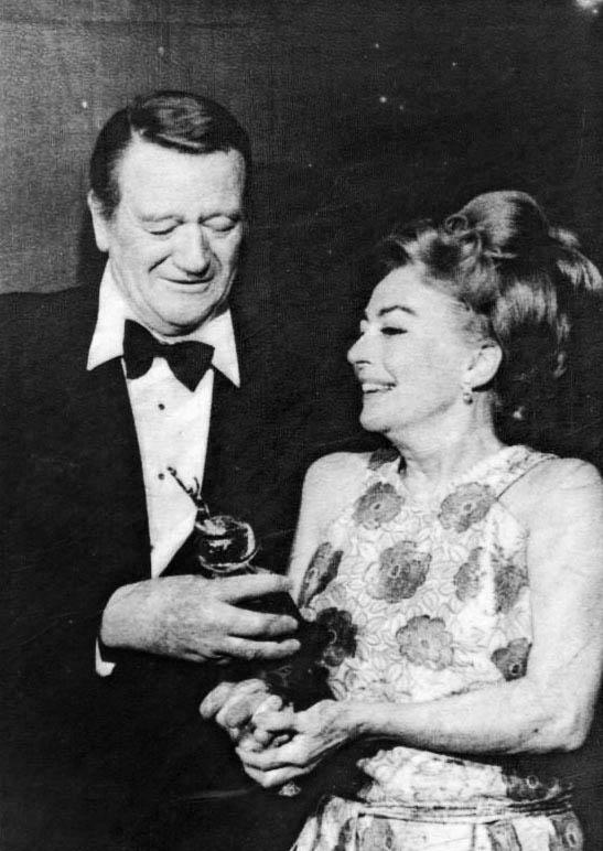 Joan receiving the Cecil B. Demille Award by John Wayne